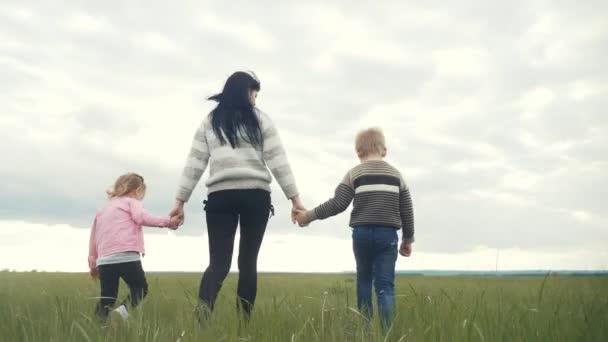 glückliche Familie. Mutter und kleine Kinder gehen im Park Hand in Hand. Frau und kleiner Junge und Mädchen gehen bei Sonnenuntergang auf einer grünen Wiese spazieren