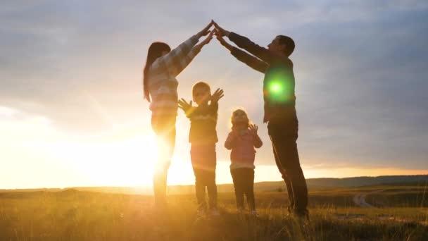 glückliche Familie. Teamwork erwachsene Eltern und kleine Kinder zeigt ein Haus und ein Komfortsymbol Silhouette bei Sonnenuntergang. glückliche Familie Mama Papa und Kinder darstellen ein Hausdach halten ihre Hände über ihre