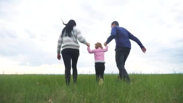 Šťastná rodina. Máma táta a malé dítě běží v parku zvednout ruce hrát týmovou práci venku držet se za ruce. žena muž a holčička životní styl zvednout ruce na zelené pole při západu slunce