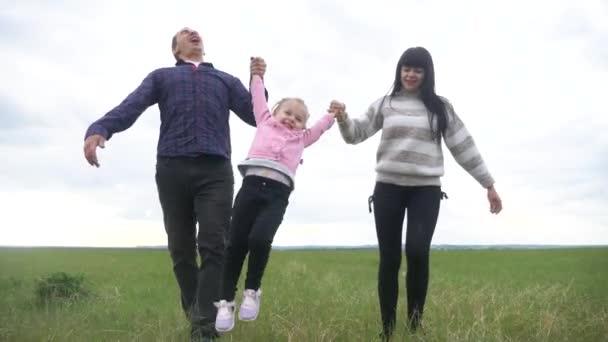 glückliche Familie. Mama Papa und kleines Kind laufen im Park und heben die Hände, spielen im Freien Hand in Hand. Lifestyle-Frau und kleines Mädchen heben bei Sonnenuntergang die Hände auf der grünen Wiese