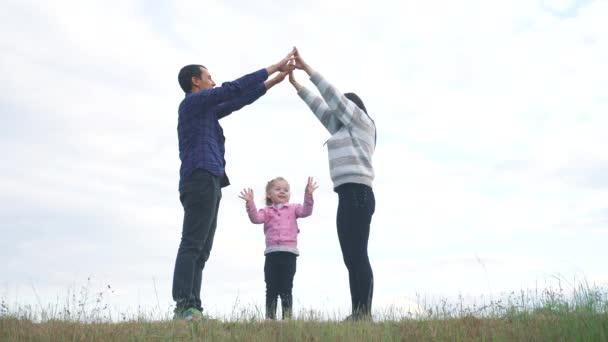 Šťastná rodina. Týmová práce Dospělí rodiče a životní styl malých dětí ukazuje dům a symbol pohodlí. šťastný rodina maminka táta a děti děti vyobrazení domu střecha držet ruce nad hlavou