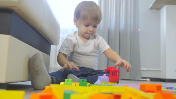 Dětství šťastný rodinný koncept holčička sbírá konstruktérské týmové práce. dítě si hraje s hračkami na podlaze. děti si hrají v týmu hračky životní styl na podlaze v místnosti
