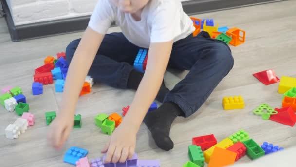Dětství šťastný rodinný koncept holčička a chlapec bratr a sestra sbírá konstruktér týmová práce. dítě hraje hračky sedící na podlaze. děti hrát v týmu hračky na podlaze v životním stylu místnosti