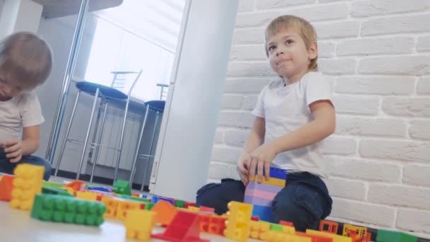 Dětství šťastný rodinný koncept holčička a chlapec bratr a sestra sbírá konstruktér týmová práce. dítě hraje hračky sedící na podlaze životního stylu. děti si hrají v týmu hraček na podlaze v místnosti