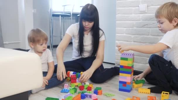 dětství šťastná rodina maminka a děti hrají koncept holčička a chlapec bratr a sestra sbírá konstruktér týmová práce. dítě hraje hračky sedící na podlaze. děti hrají životní styl v týmu