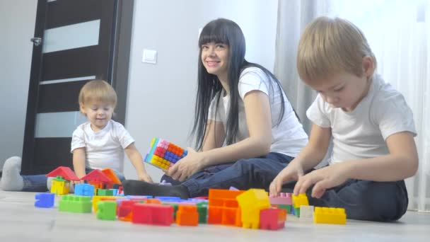 childhood happy family mom and children are playing concept little girl and boy brother and sister collects constructor teamwork. child plays toys sitting floor. children play in team toys on