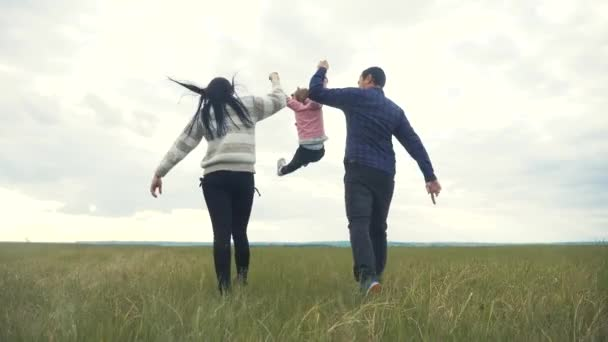 Šťastná rodina. Máma táta a malé dítě běží v parku zvednout ruce hrát týmovou práci venku držet se za ruce. žena muž a holčička zvednout ruce na zelené životní styl pole při západu slunce