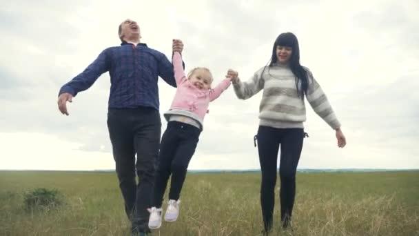 Boldog család. Anya apa és a kisgyerek egy fut a parkban emelje fel a kezét játszani csapatmunka a szabadban kéz a kézben. nő életmód férfi és kislány fel a kezét a zöld mező naplementekor