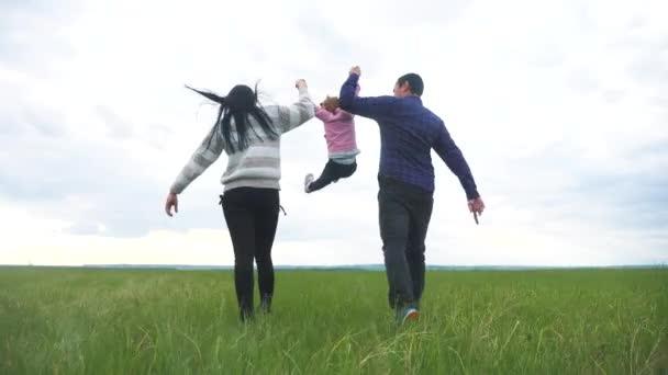 Šťastná rodina. Máma táta a malé dítě běží v parku zvednout ruce hrát týmovou práci venku držet se za ruce. žena muž a holčička zvednout ruce životní styl na zelené louce při západu slunce