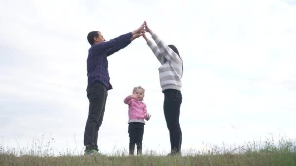 Šťastná rodina. Týmová práce Dospělí rodiče a malé děti ukazuje životní styl domu a symbol pohodlí. šťastný rodina maminka táta a děti děti vyobrazení domu střecha držet ruce nad hlavou