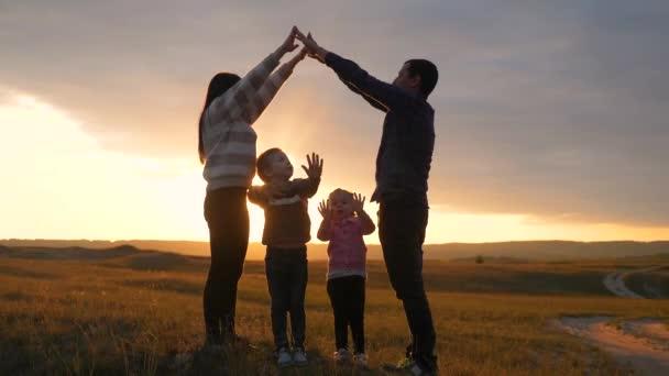Šťastná rodina. Týmová práce Dospělí rodiče a malé děti ukazuje dům a symbol pohodlí siluetu při západu slunce. šťastná rodina maminka táta a děti životní styl vyobrazení domu střecha držet za ruce