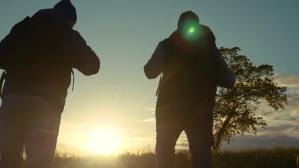 Takım çalışması. Sırt çantalı iki siluet yürüyüşçüsü gruptan ayrıldıktan sonra doğadaki ağacın tepesindeki dağlara gidecekler. Konsept seyahat macerası sağlıklı bir yürüyüş. İki kişi turist