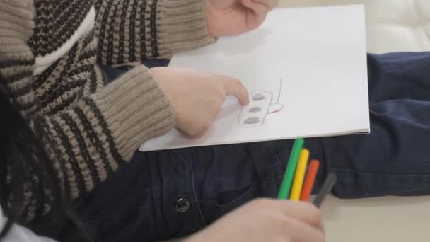 A kisfiúk és az anyák rajzolnak csapatmunkát boldog családi koncepció. Gyerek fia anyával egy nő ceruza rajzolással foglalkozik. lecke a gyermekek fejlesztése életmód kreativitás