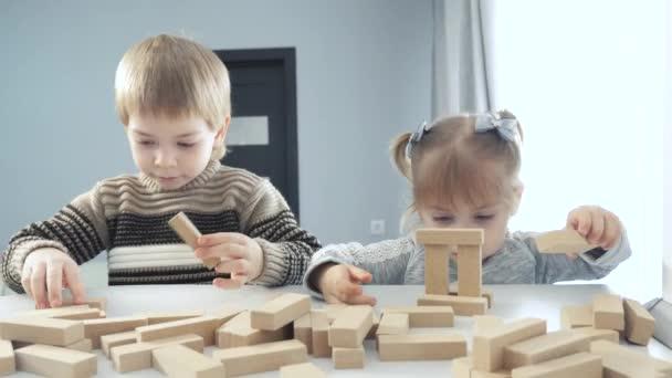 děti hrát v designérské dřevěné hole týmová práce. šťastný rodinný děti malý chlapec a dívka hrát v dřevěných blocích kostky postavit dům. bratr a životní styl sestra sbírat designér vývoj výtvarných