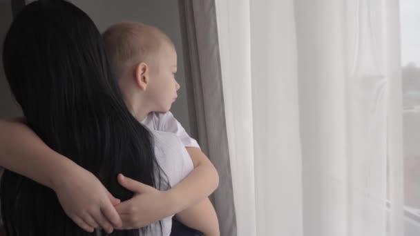 Máma drží svého syna v náručí. šťastný rodinný koncept. Máma drží malého chlapce v náručí při pohledu z okna vnitřní péče o dítě životní styl šťastný rodina