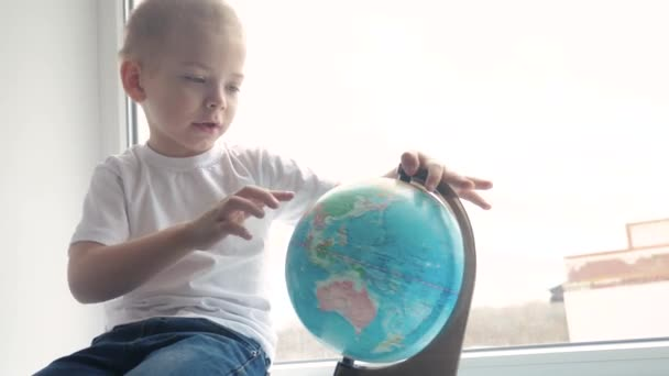 boy studies globe. education travel tourism concept. child twists the globe sits on a window sill. kid looking for a country on a globe map. lifestyle world map geography study
