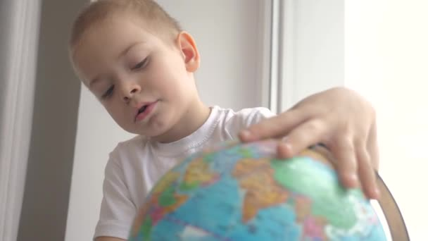 boy studies globe. lifestyle education travel tourism concept. child twists the globe sits on a window sill. kid looking for a country on a globe map. world map geography study