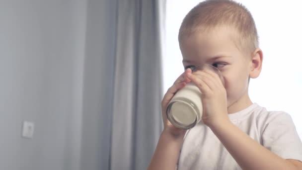 Malý chlapec pije mléko. dítě pije mléko z životního stylu sklenice vnitřní ranní snídaně