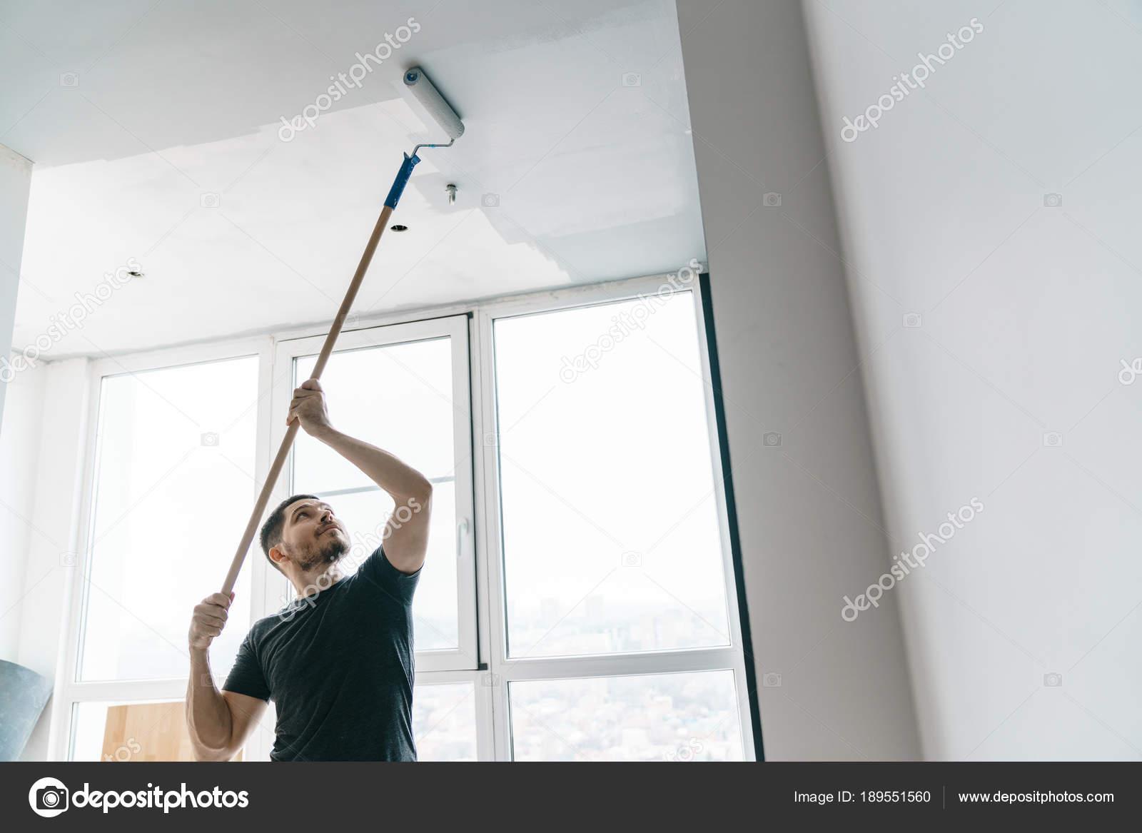 Homme Peint Les Murs Plafond Gris Sur Son Balcon Dans Photographie