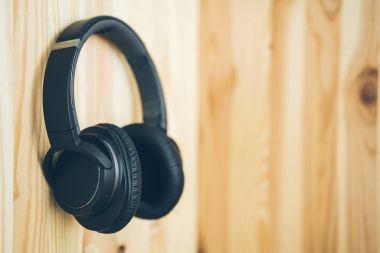 Black wireless large headphones hang on the nail on a natural wooden wall. Music and technology.