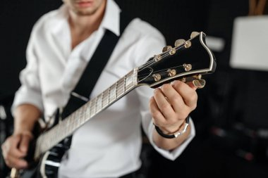 man in a white shirt holds an electric guitar in his hands and adjusts the sound.
