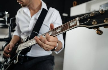 man in a white shirt on a dark background, holds an electric guitar in his hands and tunes the sound of strings.