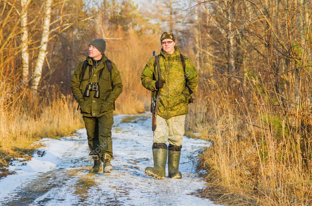 Two hunters in the forest in late autumn