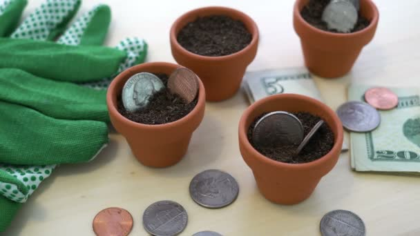 Close up shot of USA Dollar money and coins planted in pots as a concept for saving money and having it grow for the future.