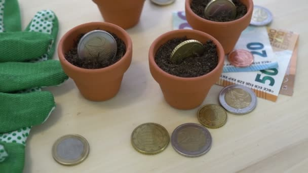 Close up shot of Euro money and coins planted in pots as a concept for saving money and having it grow for the future.