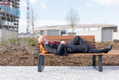 Businessman lying down on bench