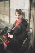 woman sitting at bus stop