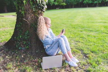 woman on grass using smartphone and notebook