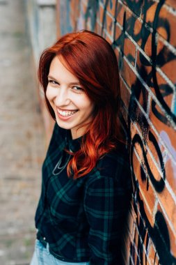 redhead woman leaning against a brick wall