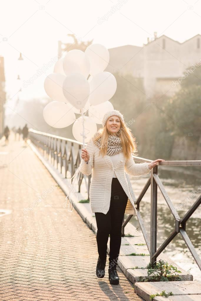 woman in city holding white balloons