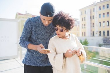 multiethnic couple using smartphone