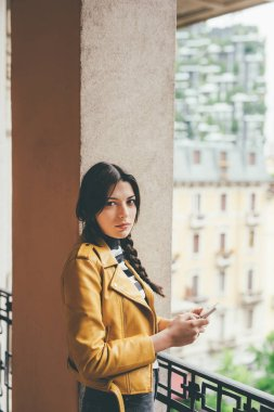 woman leaning on balcony using smartphone
