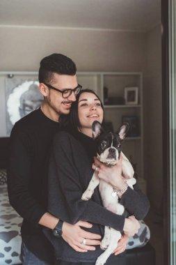 Couple holding french bulldog puppy