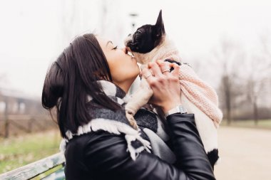 woman hugging french bulldog puppy