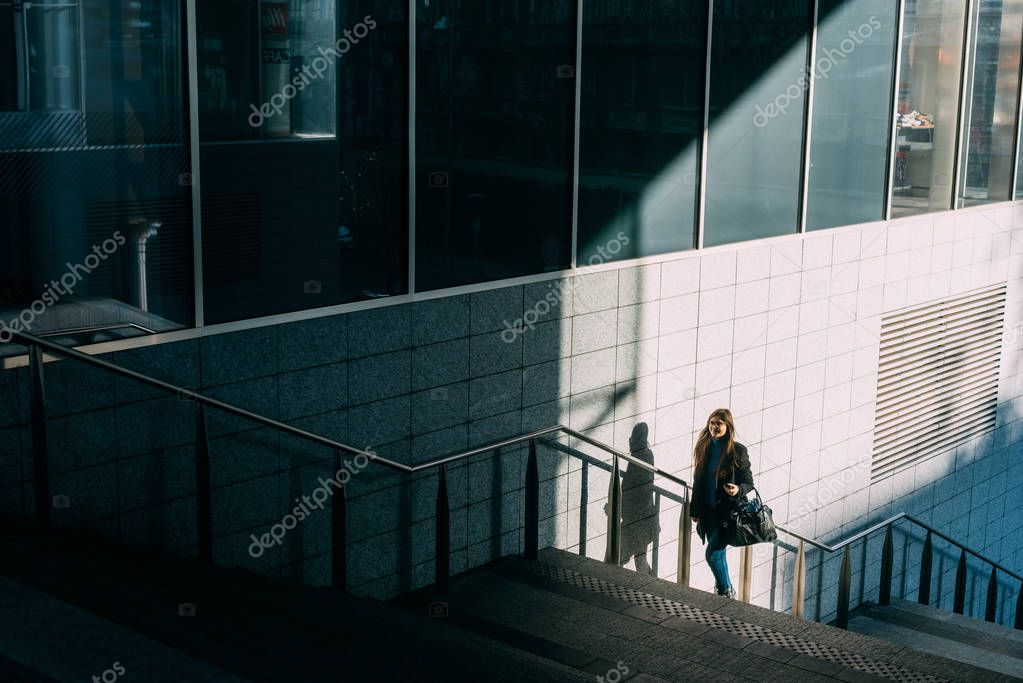 woman going upstairs holding smartphone