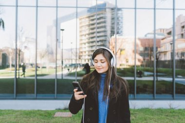 woman posing in city listening music