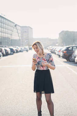 young woman outdoor back light listening music on smartphone laughing - enjoying, happiness, attitude concept