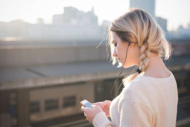 portrait young woman outdoor looking sideway listening music using smartphone - music, technology, internet concept