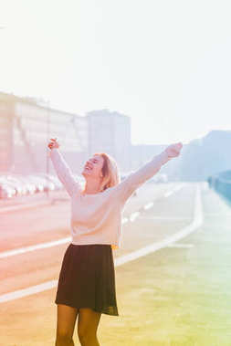 young woman outdoor back light arms raised laughing - freedom, victory, satisfaction concept - colorful filtered