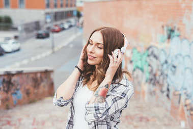 young woman outdoors listening music with headphones eyes closed - relaxing, enjoying, music concept