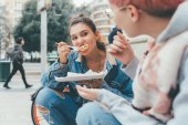 two young women outdoors eating pizza