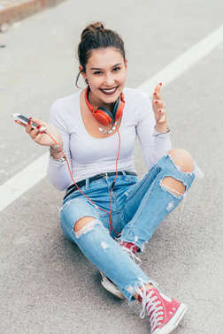 young woman outdoors listening music with headphones using smart phone - relaxing, enjoying, technology concept