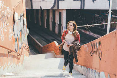 Young beautiful woman walking upstairs in the city holding smartphone