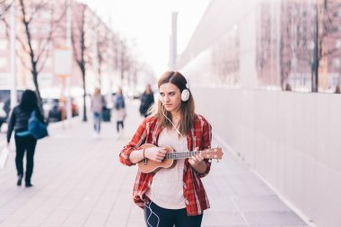 Young woman in the city playing ukulele