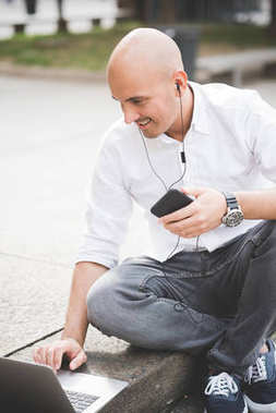 Young contemporary businessman remote working sitting outdoor in the city using smartphone and computer