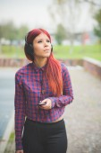 young redhead woman venezuelan listening music looking away with headphones